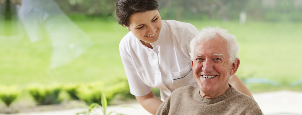 elder man smiling and female caregiver
