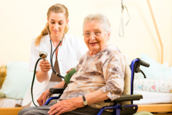 nurse checking the blood pressure of elderly woman